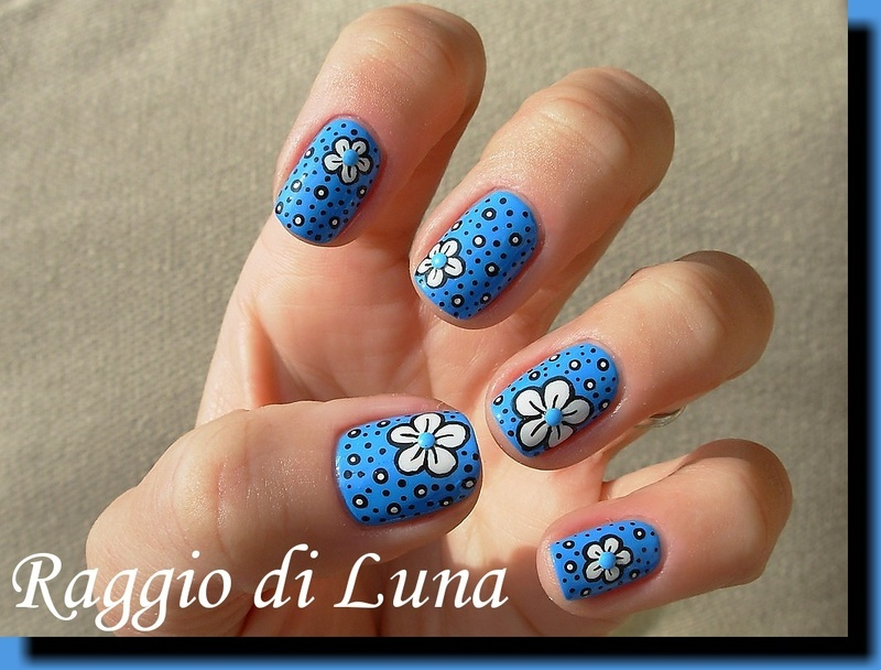 White flower with dots on sky blue nail art by Tanja