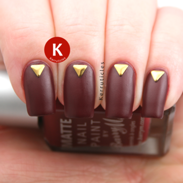 Matte burgundy with triangular gold studs nail art by Claire Kerr