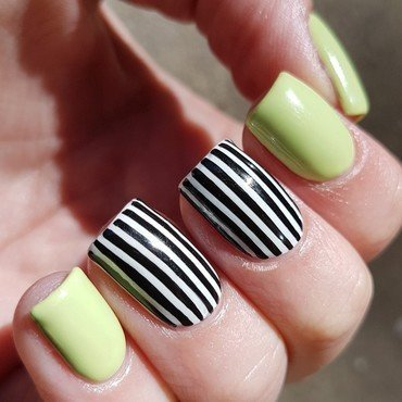 Pastel green with black and white stripes nail art by Emmelie Slotboom