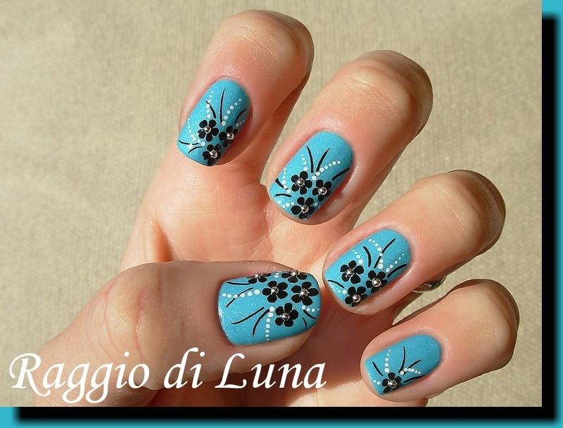 Black little flowers on light blue nail art by Tanja